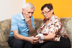 Ongerust gemaakte oudsten die bloeddruk meten Stock Foto