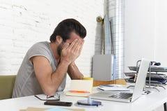 Ongerust gemaakte student of zakenman bij computer die zijn gezicht behandelen met zijn gedeprimeerd en droevige handen Stock Foto's