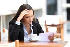 Ongerust gemaakte uitvoerende lezingsbrief in een koffiewinkel stock fotografie