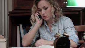Ongerust gemaakte vrouw die op de telefoonzitting op het haar werk spreken stock video
