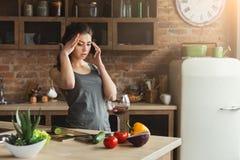 Ongerust gemaakte vrouw die op telefoon in huiskeuken spreken royalty-vrije stock foto