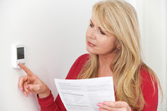 Ongerust gemaakte Vrouw met Verwarmend Bill Turning Down Thermostat royalty-vrije stock afbeeldingen