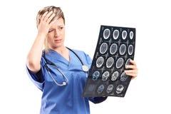 Ongerust gemaakte vrouwelijke arts die een röntgenstraal bekijken stock foto's