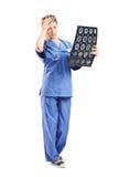 Ongerust gemaakte vrouwelijke arts die een röntgenstraal bekijken Royalty-vrije Stock Foto's