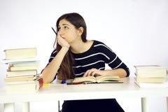 Ongerust gemaakte vrouwelijke die student door boeken wordt omringd Royalty-vrije Stock Foto