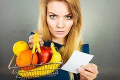 Ongerust gemaakte vrouwenholding het winkelen mand met vruchten royalty-vrije stock foto
