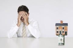 Ongerust gemaakte zakenman bij lijst met huis bovenop rekeningen die stijgende onroerende goederentarieven vertegenwoordigen Stock Foto's
