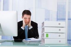 Ongerust gemaakte zakenman die bindmiddelen op bureau bekijken royalty-vrije stock afbeeldingen
