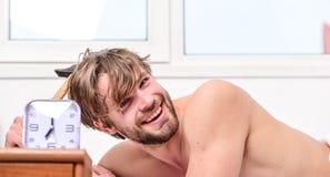 Ongeschoren de mens legt bed dichtbij wekker Stokprogramma Genoeg slaap voor hem Ochtendalarm kielzog omhoog vroeg in ochtend royalty-vrije stock foto