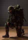 Ongewapende vrouw met camouflage op één knie De jonge vrouwelijke militair neemt met verrekijkers en rugzak waar Militaire oorlog stock fotografie