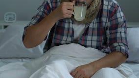 Ongezond mannetje in bed die aan griep, het drinken geneeskundevloeistof, koortsvirus lijden stock video