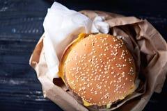 Ongezonde cheeseburger in de document container Stock Fotografie