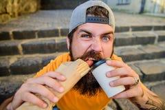 Ongezonde kost Onbezorgde hipster eet ongezonde kost terwijl treden zit Snack voor goede stemming Kerel die hotdog eten Het conce royalty-vrije stock foto's