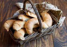 Ongezuurde broodjes in een rieten mand Stock Foto's