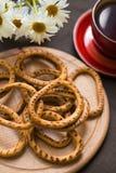 Ongezuurde broodjes op een houten bureau met thee en bloemen Stock Afbeeldingen