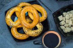 Ongezuurde broodjes op een zwarte plaat met een donkere kop van koffie en suiker op een blauw tafelkleed Stock Foto