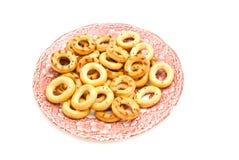 Ongezuurde broodjes op roze plaat op wit Stock Foto's