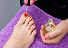 Ongle de pied de femme polissant dans le salon images libres de droits