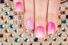 Ongles avec la manucure couverte de vernis à ongles rose sur le fond de cristaux Image stock