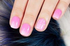 Ongles avec la manucure couverte de vernis à ongles rose sur le fond de fourrure Photographie stock libre de droits