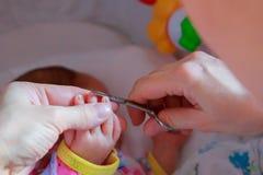 Ongles de coupe à un bébé nouveau-né qu'une petite mère s'inquiètent images libres de droits