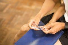 Ongles de pied de coupe de père pour son fils Image stock