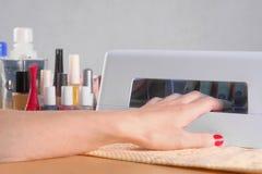 Ongles de séchage de doigt sous la lampe UV Photographie stock