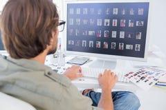 Ongles du pouce de visionnement de photographe éditeur sur l'ordinateur images libres de droits