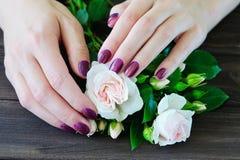 Ongles et fleurs Manicured photographie stock libre de droits