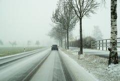 Ongunstige gevaarlijke wegvoorwaarden op een weg in de winter tijdens zware sneeuwval stock foto's