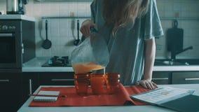 Onhandig donkerbruin meisjes gietend jus d'orange in rood glas, morserijen het overal stock video