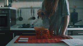 Onhandig donkerbruine vrouwen gietend jus d'orange in rood glas, morserijen het overal stock footage