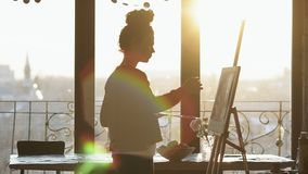 Onherkenbaar cijfer van vrouwelijke kunstenaar die op schildersezel in een kunststudio trekken met panoramische vensters Langzame stock footage
