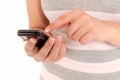 Onherkenbaar jong meisje dat een aanrakingstelefoon met behulp van Stock Foto