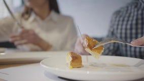 Onherkenbaar paar dat voedsel in moderne koffie dichte omhooggaand heeft De mens in de voorgrond eet pastei met vage vork en mes, stock videobeelden