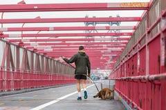 Onherkenbaar sportief recreatief mannetje jogger met zijn hond op een leiband bij de Stad van Williamsburg bridgein New York, de  stock fotografie