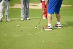 Onherkenbare Aziatische mens die op groen in golfcursus zetten Stock Afbeeldingen