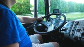 Onherkenbare bestuurderszitting achter wiel van zijn vrachtwagen en het berijden door platteland Mens het drijven aan bestemming stock videobeelden