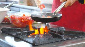 Onherkenbare chef-kok die vegetarische schotel in moderne keuken van restaurant koken Mannelijke kok die hete pan en het werpen h stock footage