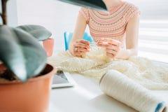 Onherkenbare craftswoman breiend iets met haakt in comfortabel werkplaats thuis binnenland Wijfje die met teder kant werken stock afbeelding
