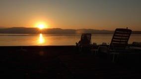 Onherkenbare eenzame vrouw die op leeg strand op de zonsopgang letten stock footage