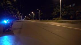 Onherkenbare fietser die een motorfiets berijden die op een weg door bomen bij nacht wordt omringd stock videobeelden