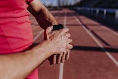 Onherkenbare jonge agentmens die slim horloge in de atletieksteeg controleren Sporten in openlucht royalty-vrije stock fotografie