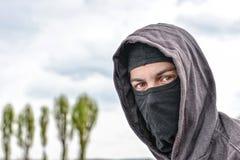 Onherkenbare jonge mens die zwarte balaclava zitting op oud dragen Royalty-vrije Stock Fotografie
