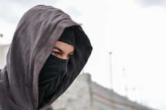 Onherkenbare jonge mens die zwarte balaclava zitting op oud dragen Stock Foto