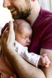 Onherkenbare jonge vader die thuis zijn pasgeboren baby houden gir stock afbeelding