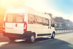 Onherkenbare kleine passenger van hurry omhoog op weg bij het verkeer van de stadsstraat met stedelijke cityscape en zonsondergan stock foto's