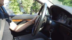 Onherkenbare mens die zijn hand op een stuurwiel en aandrijving houden een auto op de stedelijke weg op zonnige de zomerdag jong stock video