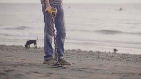 Onherkenbare mens met elektronisch het aftastenzand van de metaaldetector op het strand met metaaldetector die kostbaarheden vind stock video