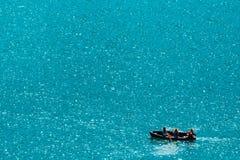 Onherkenbare mensen die in boot op meer roeien Royalty-vrije Stock Afbeelding